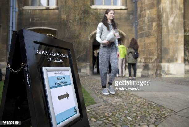 A girl with flowers walks past a queue of people queueing outside the chapel at Gonville and Caius College to write on the book of condolence...