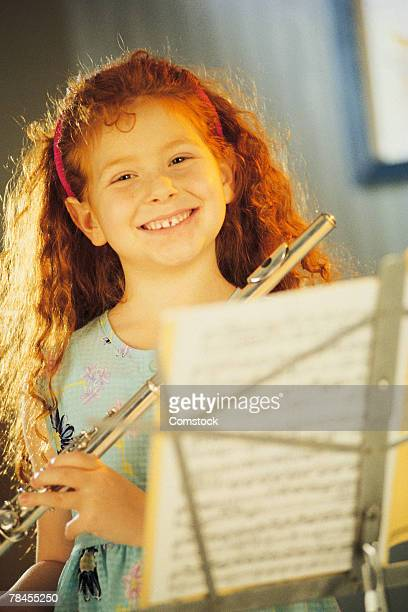 Girl with flute and sheet music on stand