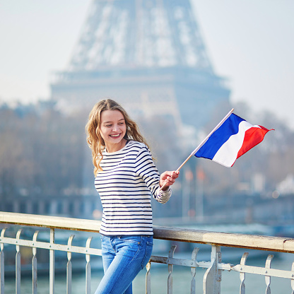 Girl with French national tricolor flag near the Eiffel tower 1014267566