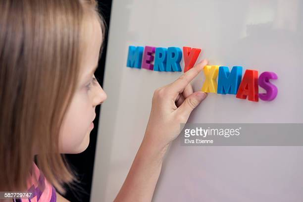 girl with fridge magnets spelling merry xmas - putting stock photos and pictures