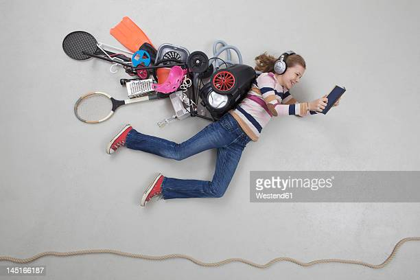 Girl with gadgets reading book