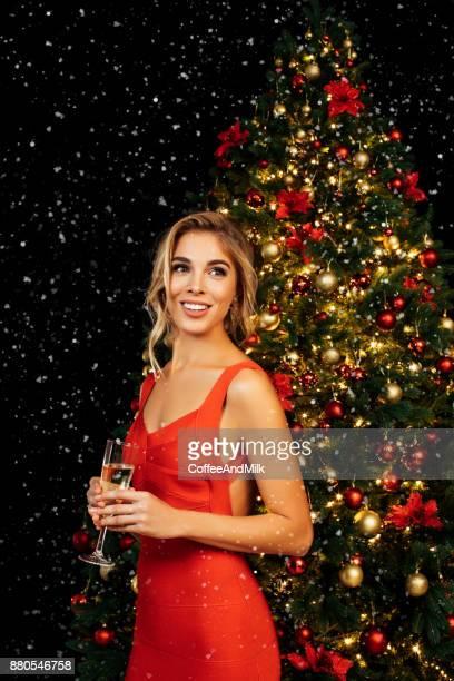 Fille avec verre de vin pétillant en face de l'arbre de Noël