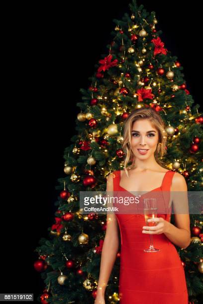 girl with glass of sparkling wine in front of christmas tree - cocktail dress stock pictures, royalty-free photos & images