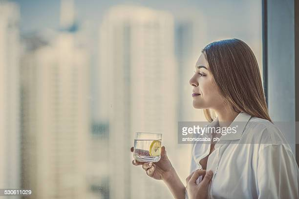 Girl with glass of water by the window