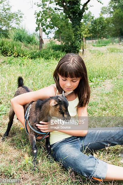 Girl with goat kid in field