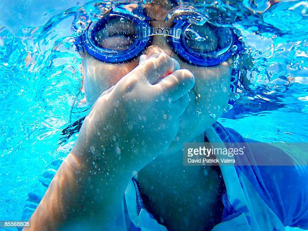 Girl With Goggles Under Water Holding Breath