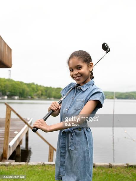 Girl (8-10) with golf club, portrait