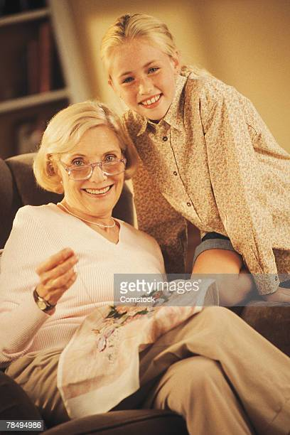 Girl with grandmother doing needlepoint