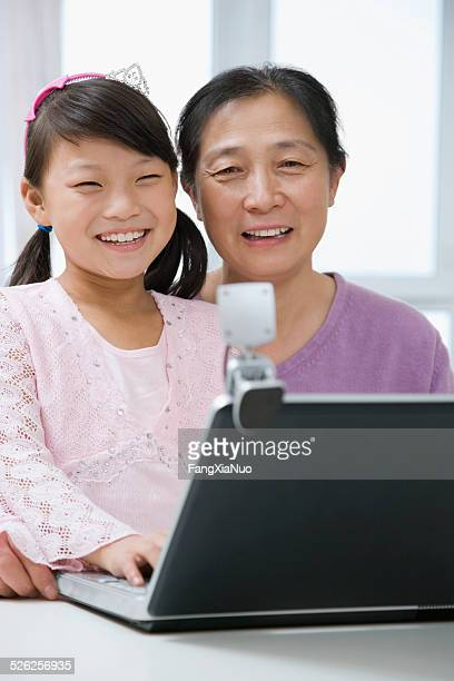 Girl with grandmother using laptop and looking into webcam