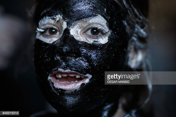 A girl with grease smeared on her face performs as a 'Diablo de Luzon' during the carnaval in Luzon near Guadalajara on February 25 2017 / AFP PHOTO...