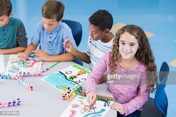 Girl with group of boys in art class smiling