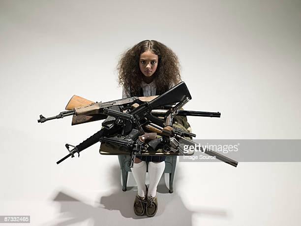 Girl with guns on her desk