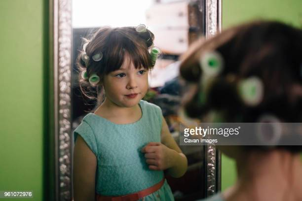 girl with hair curlers reflecting on mirror while standing at home - girl in mirror stock photos and pictures