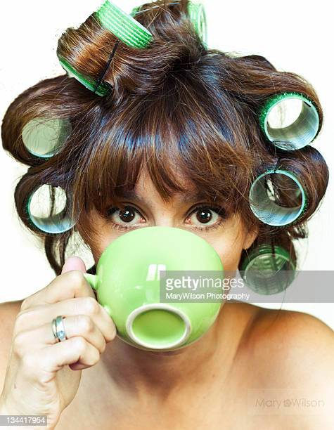 Girl with hair rollers drinking coffee