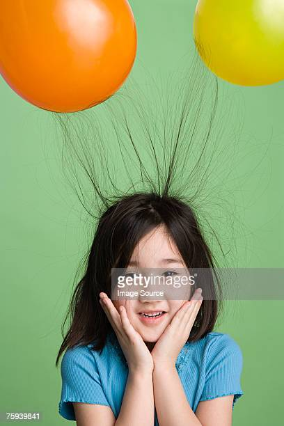 Girl with hair sticking to balloons