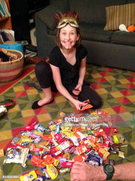 girl with halloween candy - pile of candy stock photos and pictures