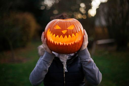 A girl with Halloween pumpkin in front of her head - gettyimageskorea