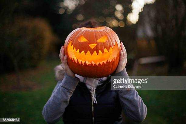 a girl with halloween pumpkin in front of her head - halloween fotografías e imágenes de stock