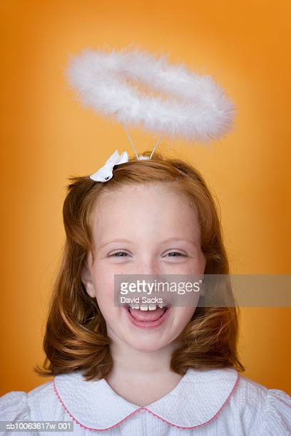 Girl (8-9) with halo over head, laughing, portrait