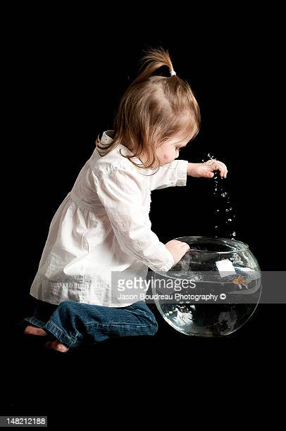 Girl with hand in fish bowl