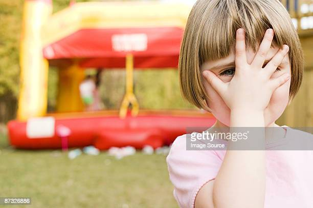 Girl with hand in front of face