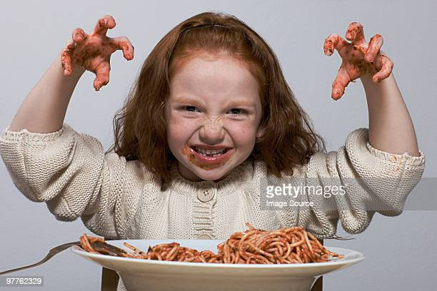 Girl with hands covered in spaghetti sauce
