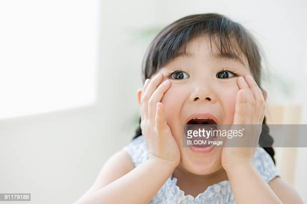 girl with hands on cheeks and mouth open - girls open mouth stock photos and pictures