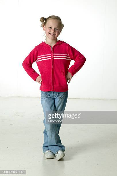 girl (6-7), with hands on hips, posing in studio, portrait - hands in her pants fotografías e imágenes de stock