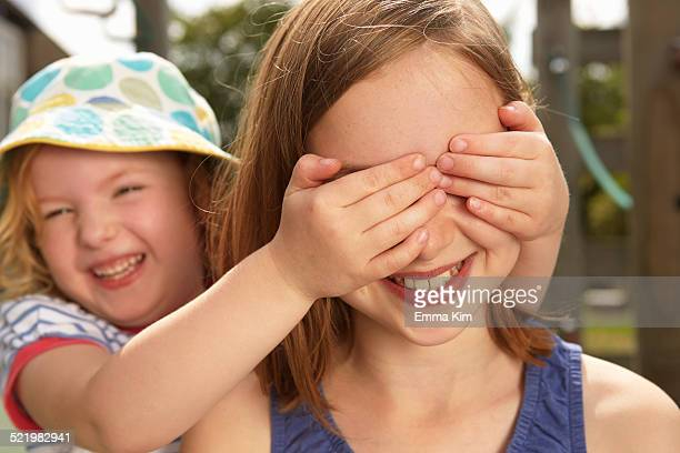 girl with hands over her sisters eyes in garden - borough of lewisham stock pictures, royalty-free photos & images