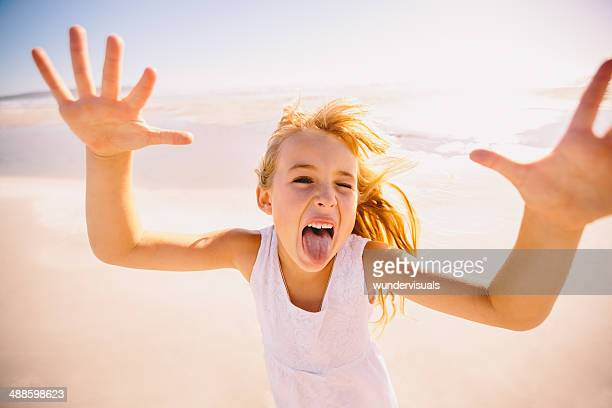 girl with hands up making funny face - little girl sticking out tongue stock photos and pictures