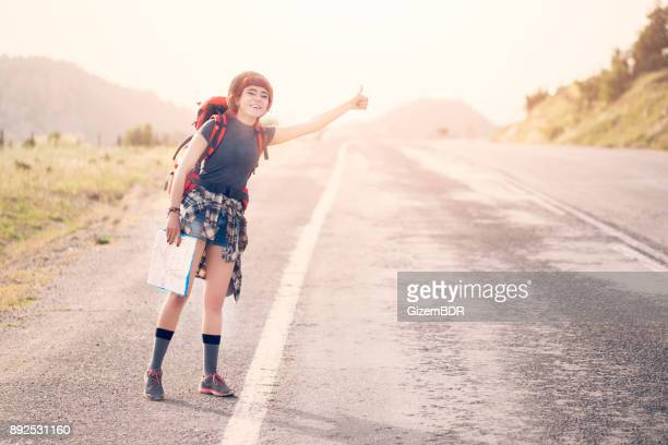 girl with hat and backpack hitchhiking on the road - hitchhiking stock pictures, royalty-free photos & images