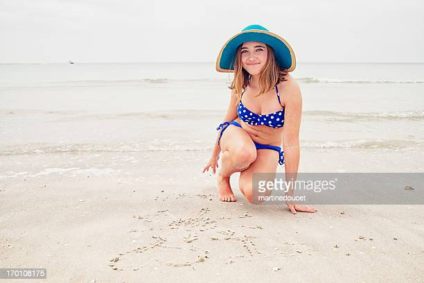 Girl with hat and bikini writing on beach.