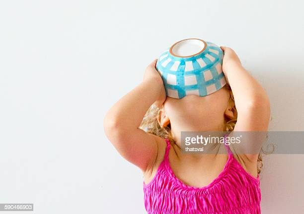 girl with head back holding cereal bowl to her mouth - hongerig stockfoto's en -beelden