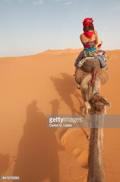 Girl with head scarf riding camel