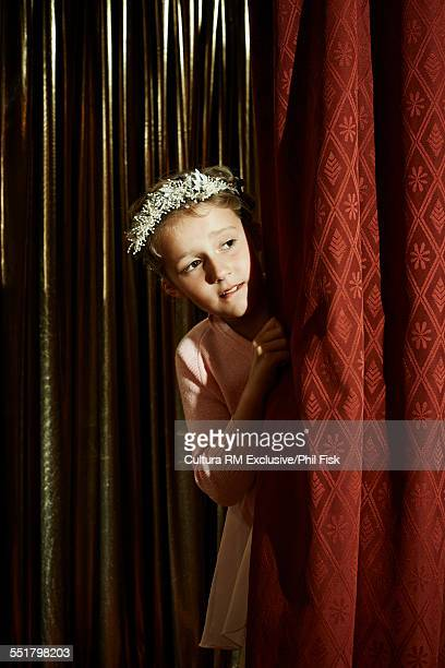 Girl with head wreath behind stage curtain