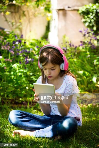 girl with headphones and digital tablet in garden - larissa veronesi stock-fotos und bilder