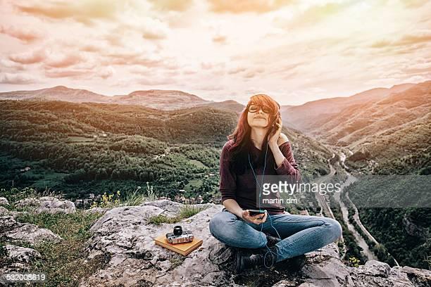 Jeune fille avec casque et smartphone sur la montagne