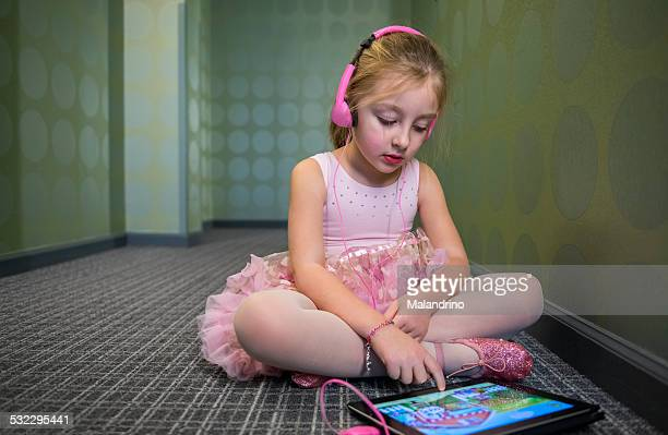 Girl with headphones playing with a tablet