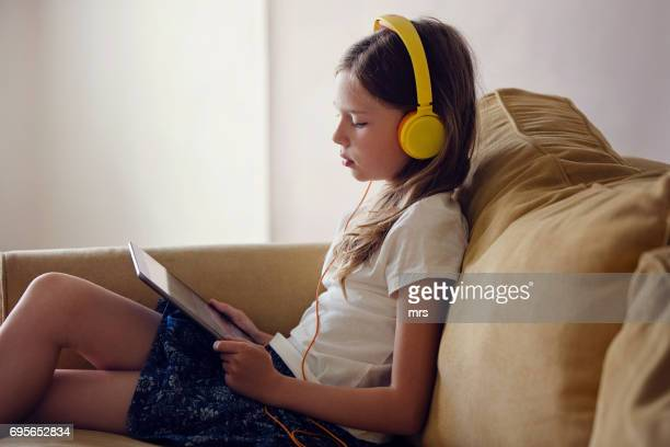 Girl with headphones using digital tablet at home