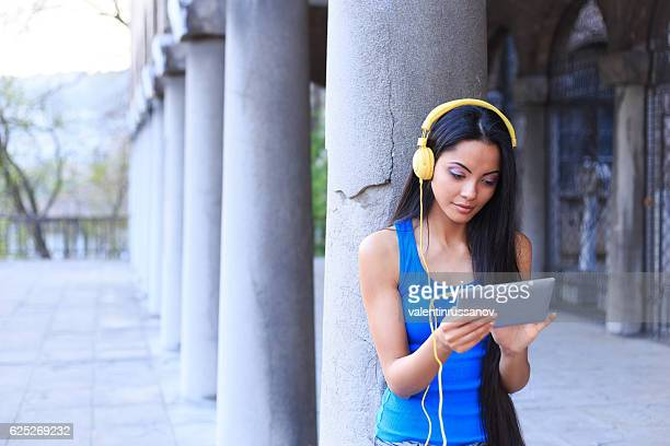 Girl with headphones using digital tablet next to ancient columns