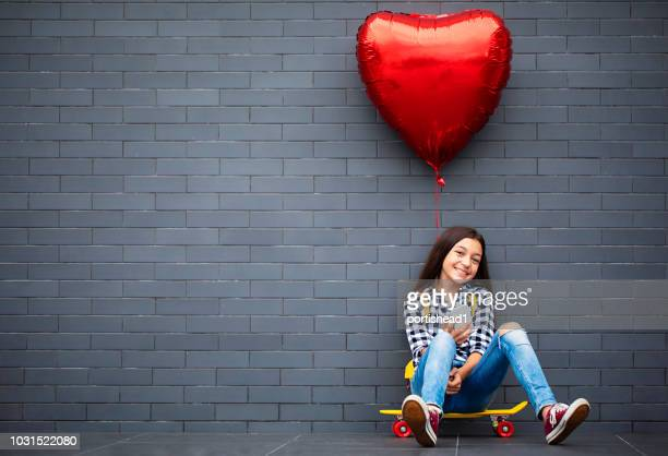 girl with heart shape air balloon - digital native stock pictures, royalty-free photos & images