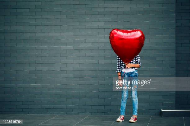 girl with heart shape balloon - heart shape stock pictures, royalty-free photos & images
