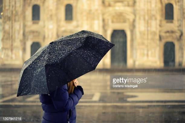 girl with heavy jogger in winter sheltering from snow and rain at night illuminated by lampposts with an umbrella - piazza del duomo milano foto e immagini stock