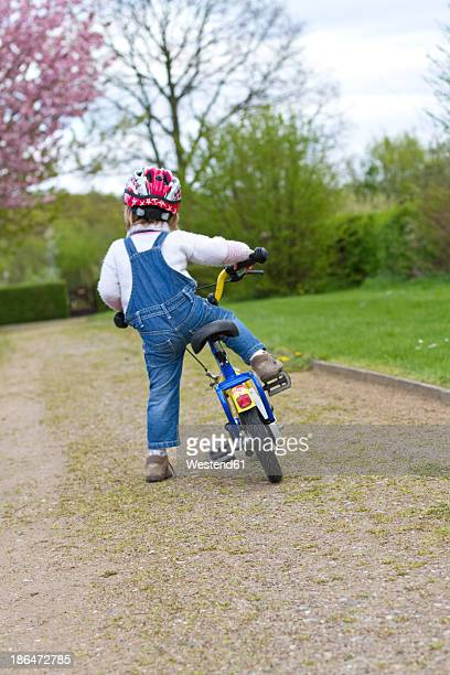 Girl with helmet driving bicycle