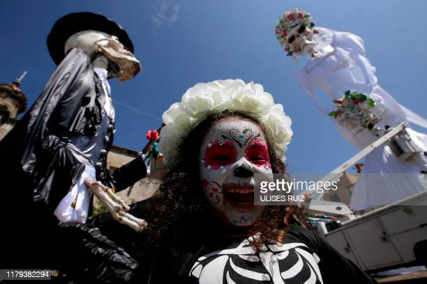 A girl with her face painted as a Catrina poses with a 20meterhigh Catrina figure the biggest in the world dressed up as a bride and the Catrin her...