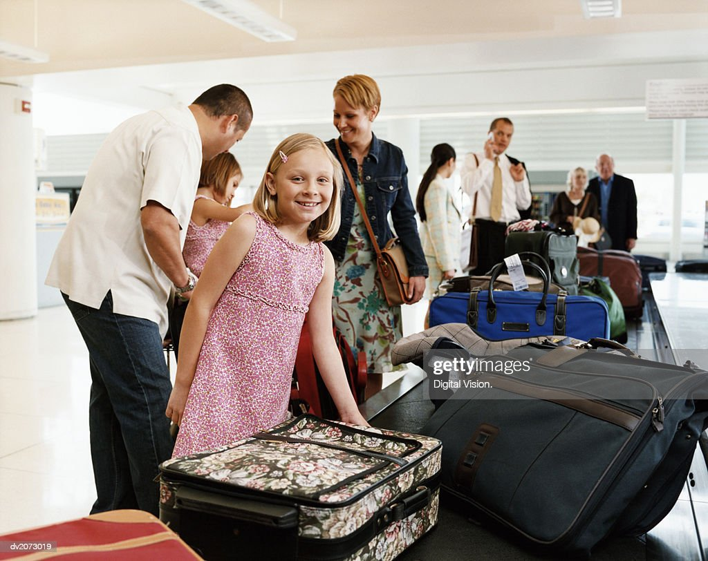 Girl With Her Family Collecting Luggage From an Airport Conveyor Belt : Stock Photo