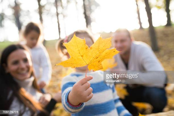 Girl with her family holding autumn leaf