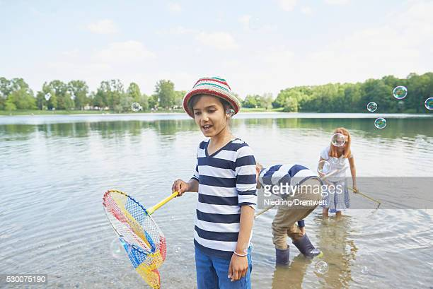 Girl with her friends catching soap bubbles with fishing nets, Bavaria, Germany,