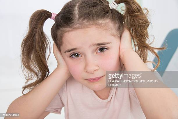 Girl with her hands over her ears