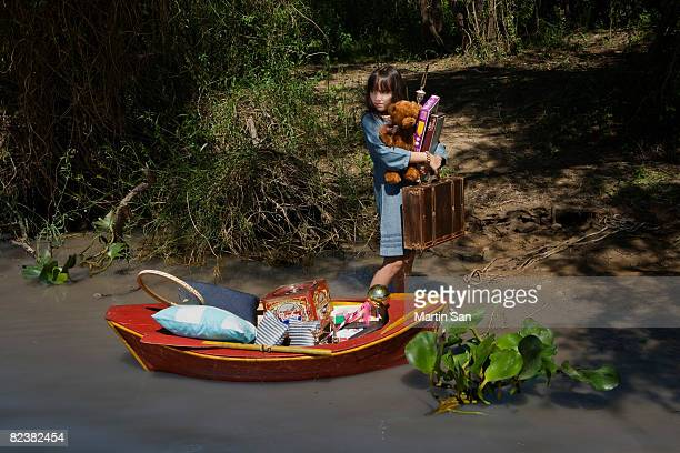 Girl with her possessions in canoe